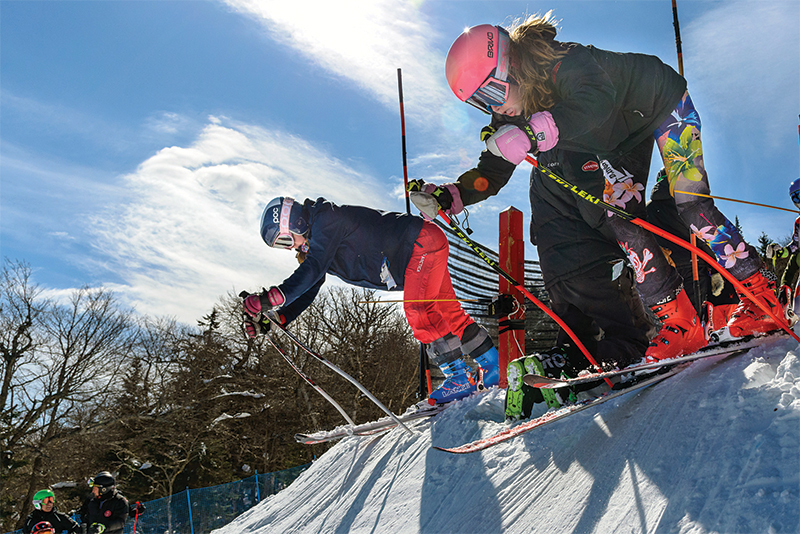 young girls a starting gate on skis