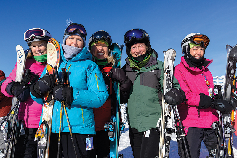 group of women outside holding skis