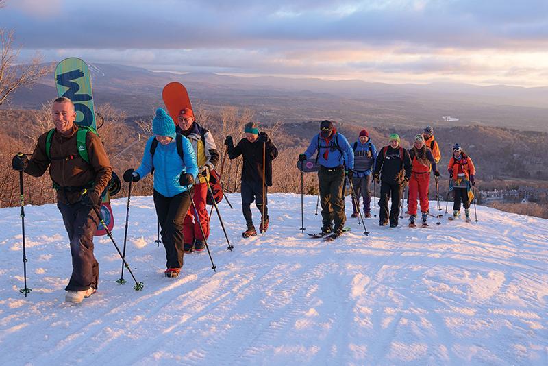 uphill hiking snowboarders